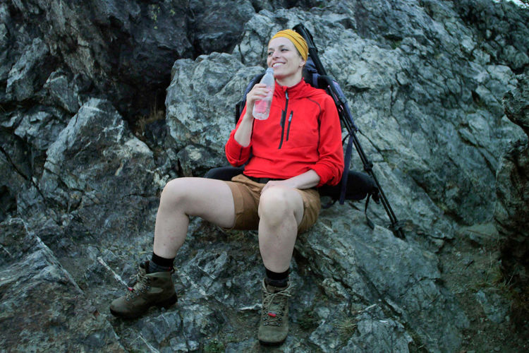 female hiker drinking water Alpine Backpacking Boots Camping Expedition Freedom Hiking Hydration Travel Trekking Woman Active Adult Adventure Backpack Bottle Caucasian Day Drinking Female Fitness Front View Full Length Happiness Leisure Activity Lifestyles Nature One Person Outdoors People Rock Rock - Object Sitting Smiling Solid Sport Trail Water Young Adult