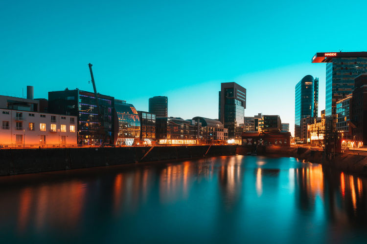 Illuminated buildings by river against blue sky at dusk