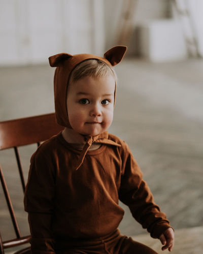 Toddler baby boy in funny costume with ears sitting looking at the camera