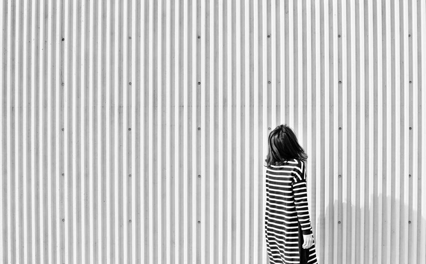 Rear view of woman standing in front of corrugated iron