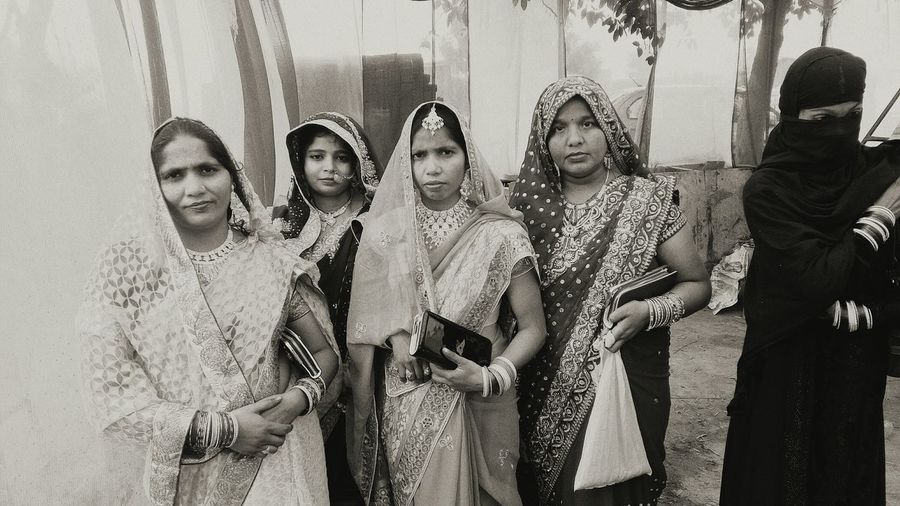 Women In Traditional Clothing Standing On Footpath