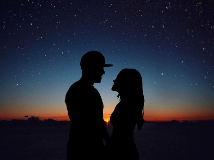 Silhouette romantic couple standing face to face on field against star field