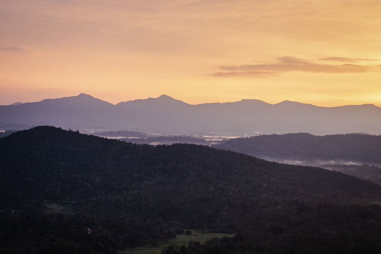 Mountains range misty shadow with dramatic colorful sunset sky at dusk from flat angle