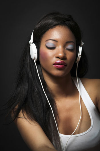 Woman Listening Music Against Black Background