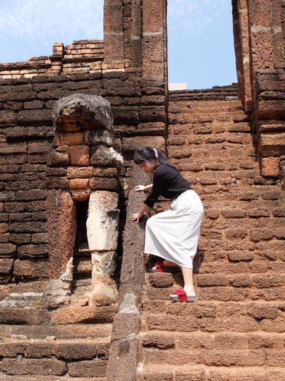 Side view of woman standing on steps leading towards old ruin