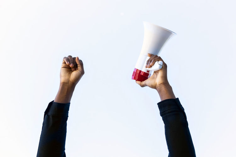 Midsection of woman holding drink against white background