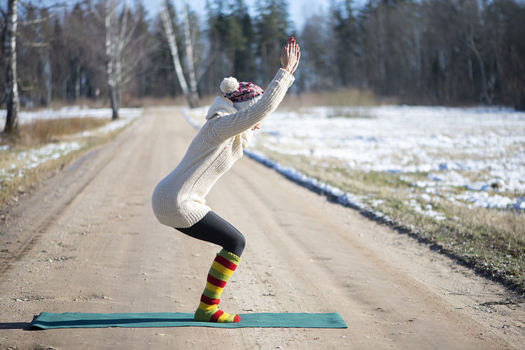 Young attractive woman practicing yoga on the rural road.outdoor activity. practice yoga asana.