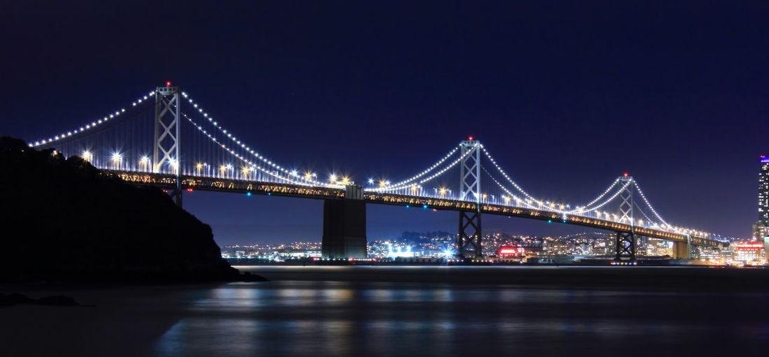 Illuminated san francisco–oakland bay bridge over sea against sky at night