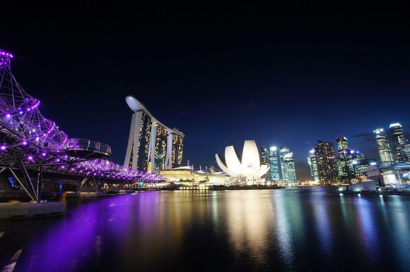 Illuminated marina bay sands with city against clear sky at night