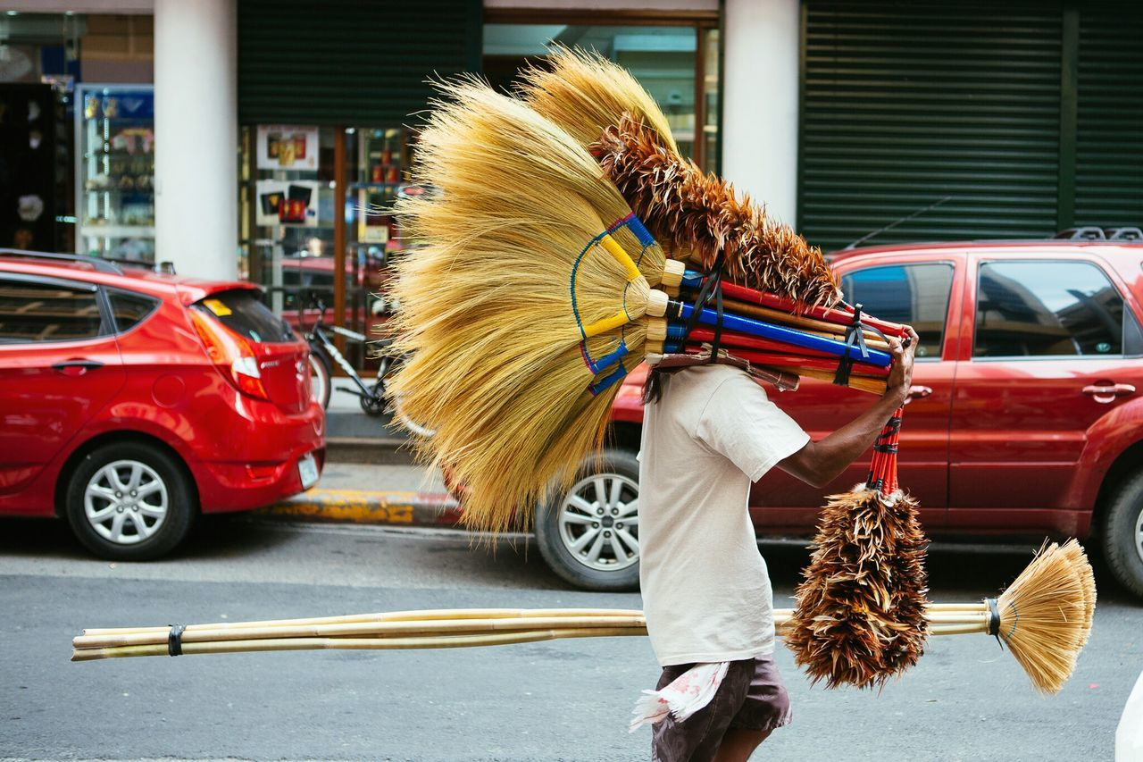 Side view of man with brooms walking on street