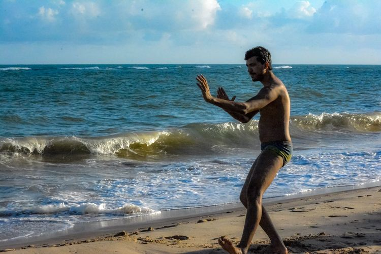 A person training tai chi chuan on the beach at sunset