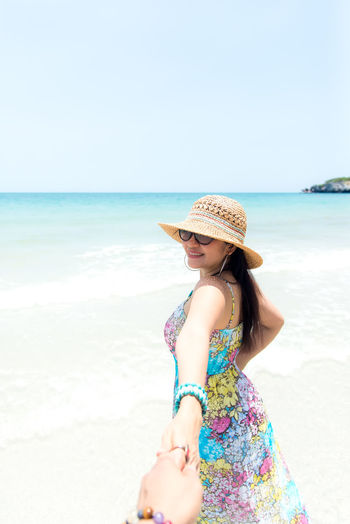 Woman wearing hat on beach against clear sky