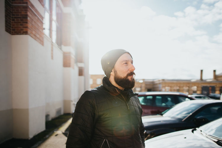 Young bearded man looking away in city