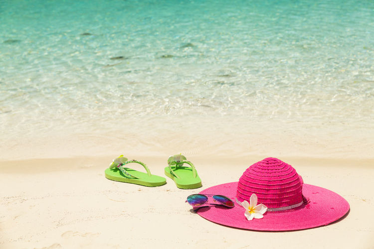 Flip flops and sun hat on sand at beach