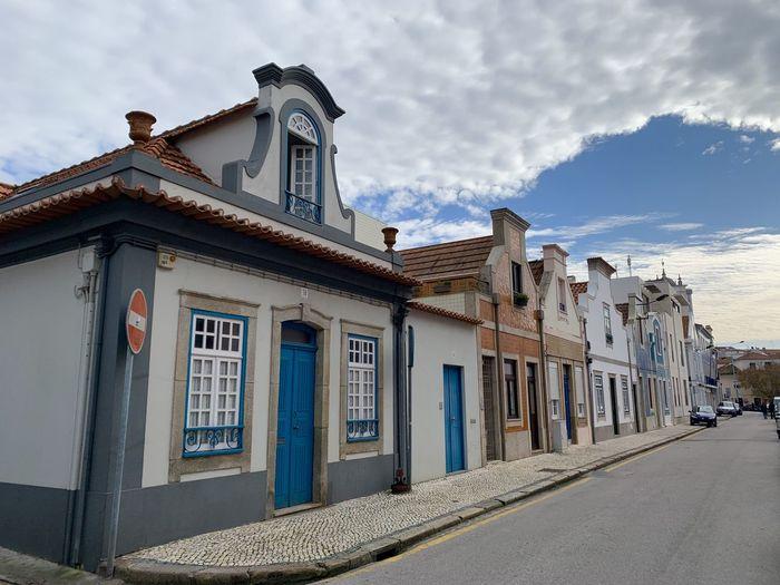 Buildings by street in town against sky