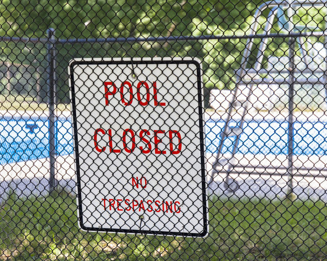 Pool Closed Sign. Community No Trespassing Signage Barrier Boundary Chainlink Fence Closed Day End Of Summer Fence No People Outdoors Pool Pool Closed Sky Swimming Pool