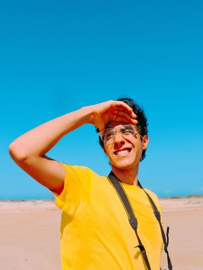 Portrait of smiling man standing on beach against clear blue sky