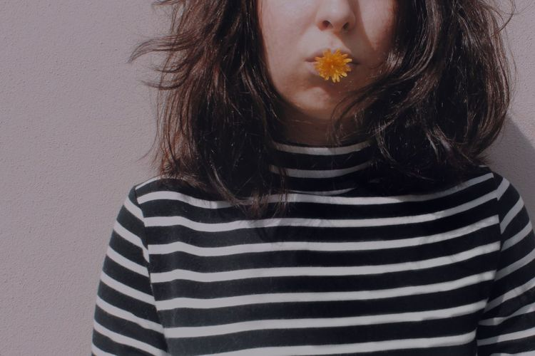 Midsection of woman holding flower in mouth