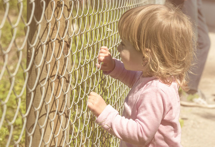 Little blonde girl holding with both hands a metal fence on a beautiful sunny day Children Emotions Human Rights Security Affection Blond Hair Chainlink Fence Child Childhood Feelings Fence Fenced Little Girl Privacy
