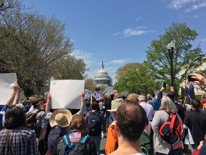 Rear view of crowd protesting at capitol building against sky