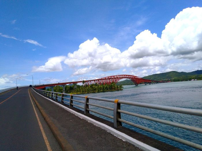 View of bridge over road against cloudy sky