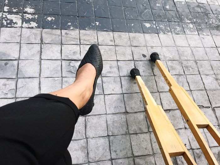 Low Section Of Woman By Walking Cane On Walkway