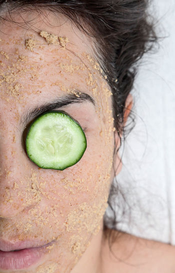Close-up of woman with facial mask and cucumber