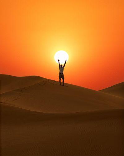 Man standing on sand dune against sky during sunset