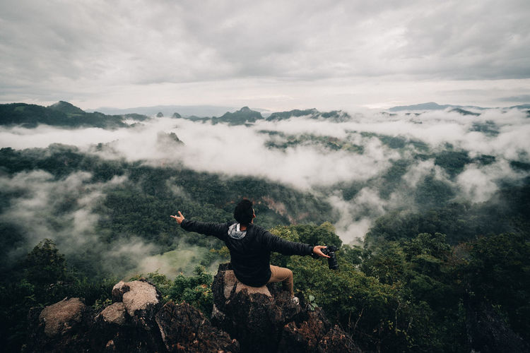 Rear view of man sitting against mountains during foggy weather