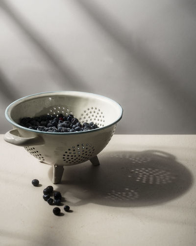 Close-up of blueberries in colander on table