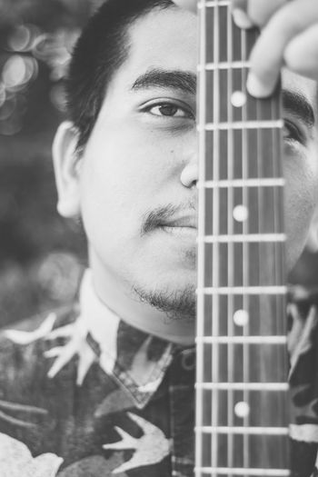 One Person Musical Instrument Portrait Music Young Men Young Adult String Instrument Real People Holding Headshot Guitar Front View Leisure Activity Lifestyles Close-up Arts Culture And Entertainment Musical Equipment Men Human Face