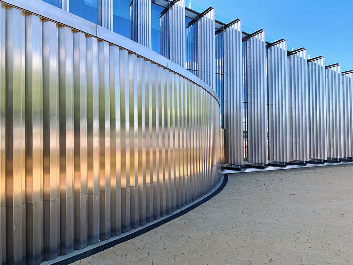 Metallic structure on footpath against building