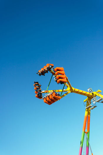 Low angle view of amusement park ride against clear blue sky