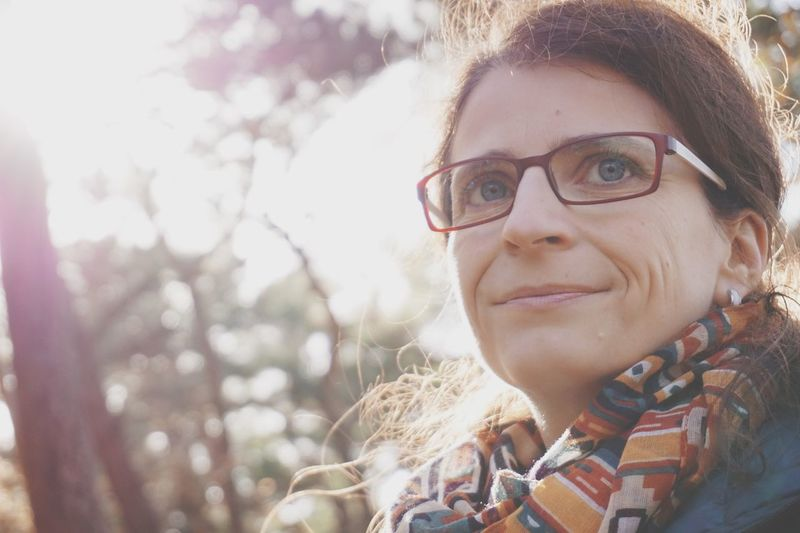 Close-up of smiling woman looking away sitting against trees