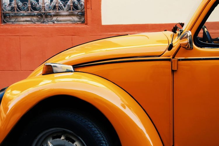 Close-up of vintage car parked against orange wall
