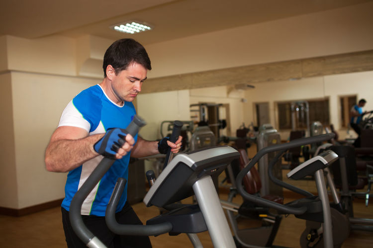 Young man exercising on machine in gym