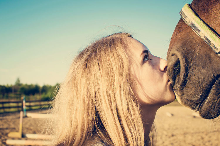 Blond Hair Clear Sky Day Girl And Horse Girl Portrait Headshot Horse Horse Head Kissing One Person Outdoors People People And Animals Real People Sky Summer Day Training Ground Young Adult Young Woman Visual Creativity