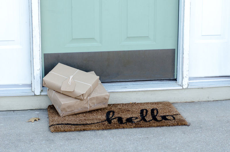 Christmas packages waiting on the doorstep wrapped in brown paper and tied with string