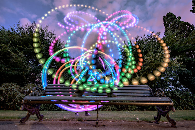 Abstract Light Designs Over Bench In Park At Dusk
