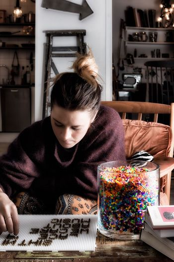 Young Woman Playing With Beads At Home