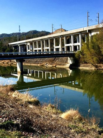 Architectural Structure : Bridges - The Elevated Railway for Superexpress Train and the Bridge for Townspeople. Bridge - Man Made Structure Water Reflection Clear Sky Nature River Outdoors No People Mountain grass Taken in Higashi-Hiroshima , Japan on Jan. 28, 2017. (Submitted on March 21, 2017)