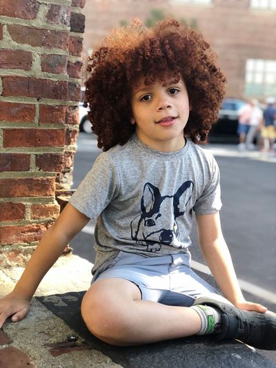 Boy Mixed Race Afrohair Redhead Real People Child Leisure Activity Curly Hair Lifestyles Childhood One Person Sitting Hairstyle Casual Clothing Portrait Brick Wall Looking At Camera Front View