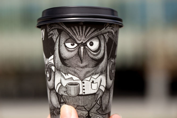Black paper disposable coffee cup with a drawn owl in hand on a blurred background outdoor Focus On Foreground Creativity Close-up Art And Craft Representation Fun Day One Animal Bird Humor Coffee Coffee - Drink Coffee Cup Coffee Time Coffee Break Cup Cup Of Coffee Paper Cup Disposable Disposable Cup Owl Owl Eyes Owl Art
