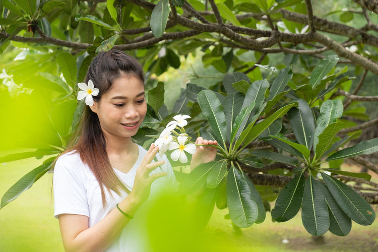 Smiling young woman against plants
