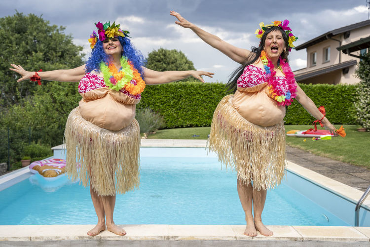 Portrait of women wearing traditional clothing dancing at poolside