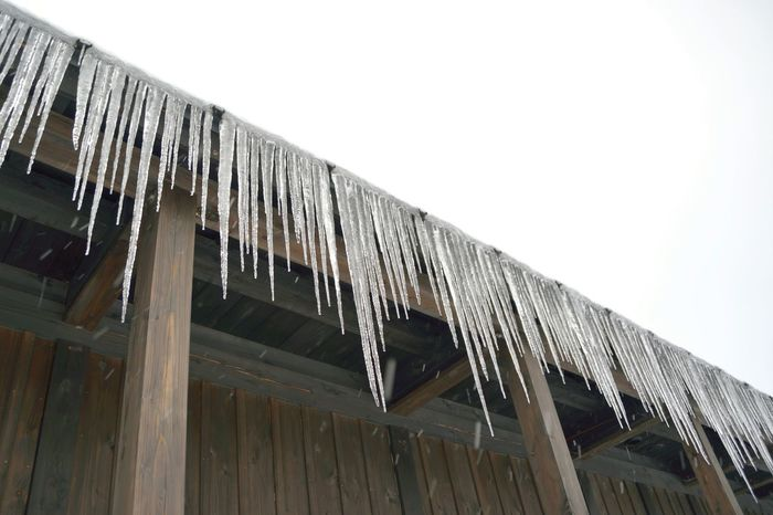 Icicles hanging from the eaves of a wooden building. Akita Architectural Feature Architecture Building Built Structure Cold Day Eaves Exterior High Section Icicle Icicles Icicles Hanging Japan Low Angle View Modern No People Outdoors Repetition Sky Winter Winter Wonderland Wood - Material