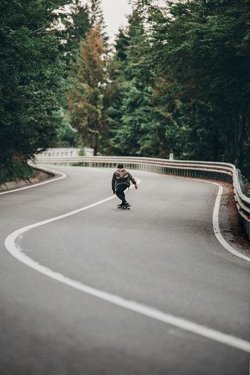 Rear view of boy skateboarding on road
