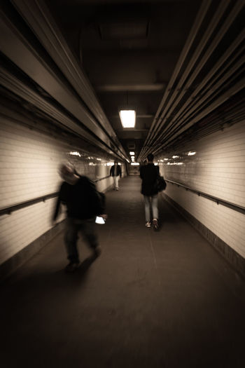 Rear view of people walking in illuminated tunnel