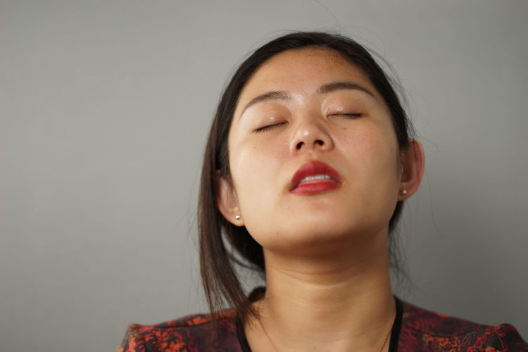 Young Woman With Eyes Closed Standing Against White Background
