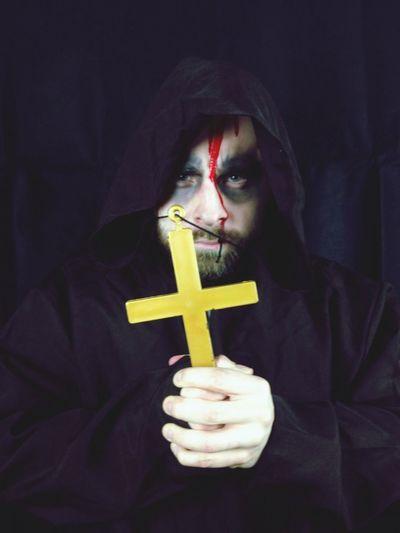 Portrait of spooky priest holding cross
